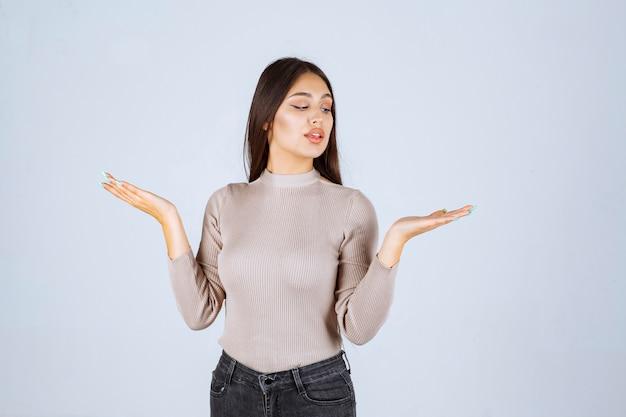 彼女の手に何かを示している灰色のセーターの女の子。