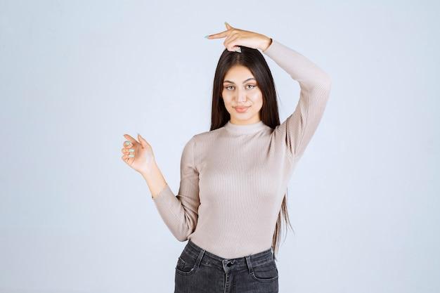 Девушка в сером свитере показывает что-то слева.