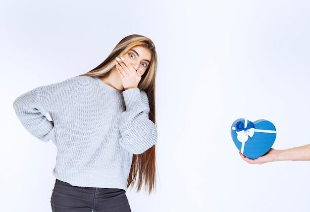 Девушка в серой толстовке удивлена подарочной коробкой в форме синего сердца.