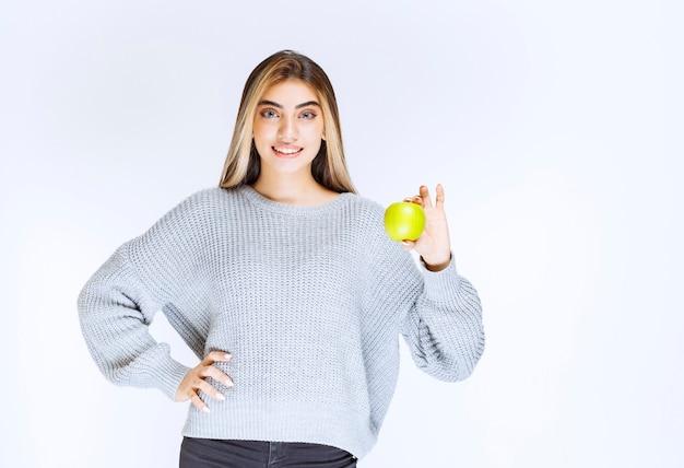Девушка в серой толстовке, держа в руке зеленое яблоко.