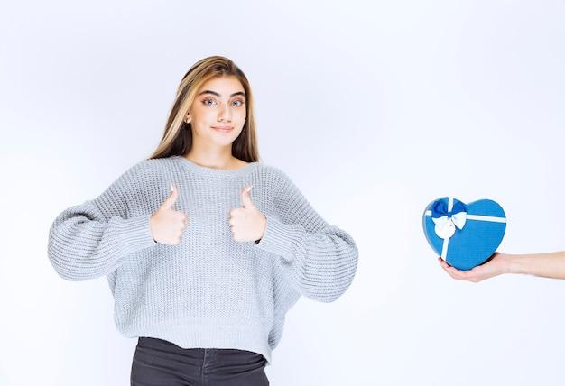 灰色のスウェットシャツを着た女の子は青いギフトボックスを提供されており、彼女は親指を立てています。