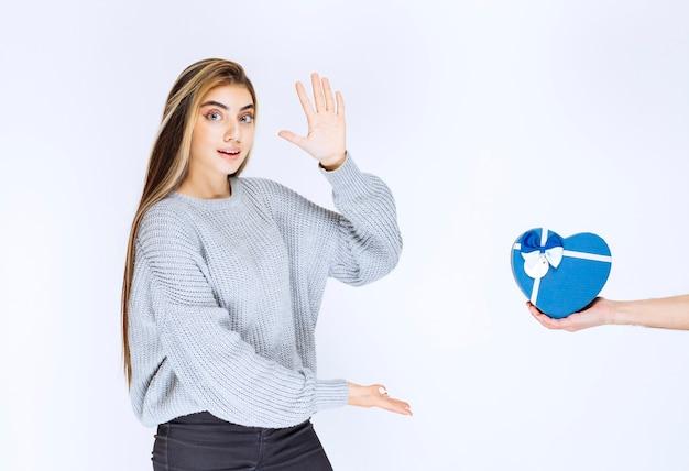 青いハート型のギフトボックスを取ることを切望している灰色のスウェットシャツの女の子。