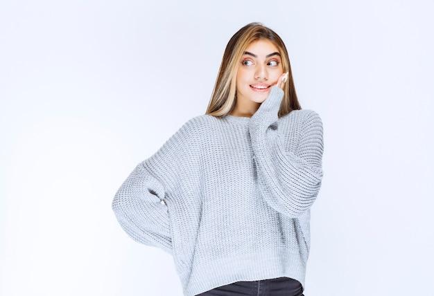 灰色のスウェットシャツの女の子は積極的に驚いているように見えます。高品質の写真