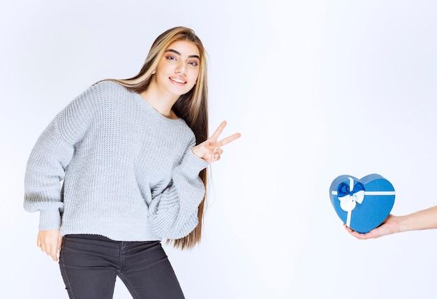 平和と友情のサインを示す灰色のスウェットシャツの女の子。