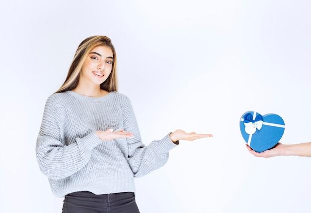 Девушка в сером свитшоте показывает подарочную коробку в форме синего сердца, которую ей предлагают.