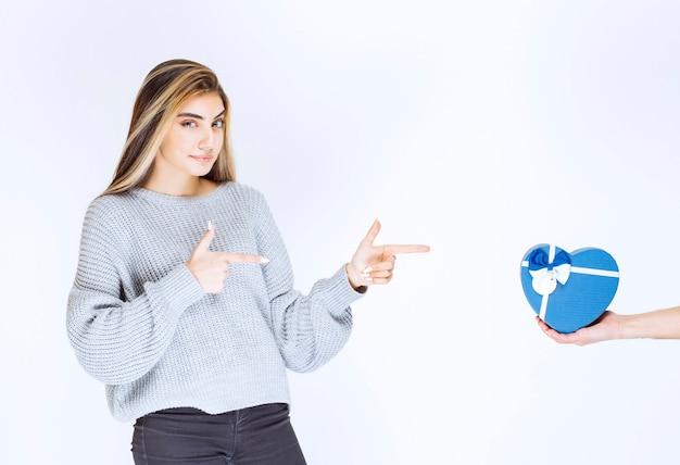 彼女に提供されている青いハート型のギフトボックスを示す灰色のスウェットシャツの女の子。