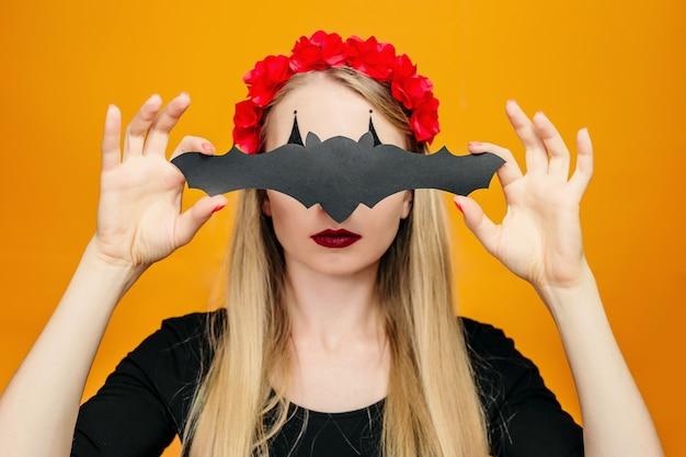 Девушка в костюме хэллоуина закрывает глаза бумажной летучей мышью, изолированной на оранжевом