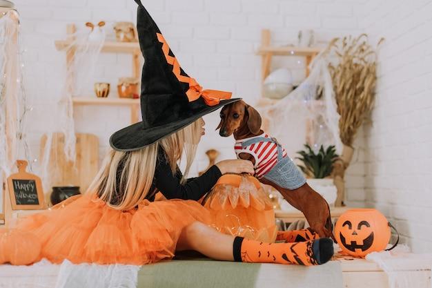 Девушка в костюме ведьмы на хэллоуин и крошечная такса в собачьем комбинезоне сидят на полу в комнате