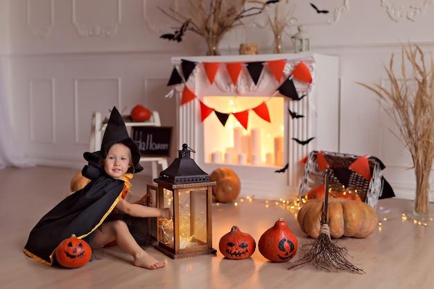 Девушка в костюме ведьмы на хэллоуин с тыквами