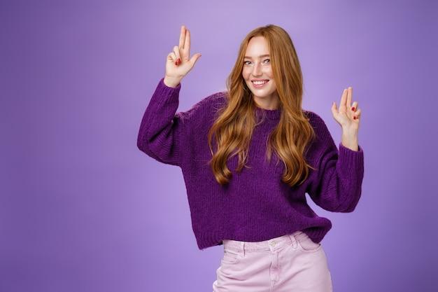행복하고 활기찬 분위기에서 춤추는 소녀는 보라색 벽 위에 보라색 스웨터를 입고 포즈를 취하는 멋진 파티에서 흥분되고 즐거운 카메라를 향해 미소 짓는 것처럼 손가락 권총 제스처를 만드는 재미를 가지고 있습니다.