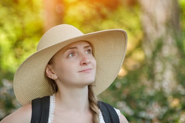 자연을 즐기는 모자에 소녀입니다. 여름 정원