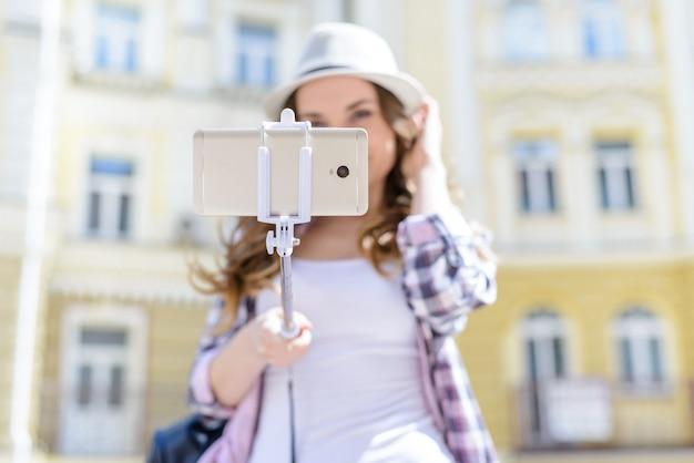 スマートフォンで自撮り棒を保持している帽子の少女