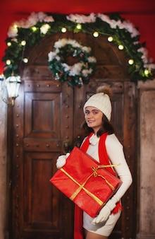 カメラを見て笑顔の赤い贈り物を保持している帽子の白いドレスの女の子クリスマスまたは新年