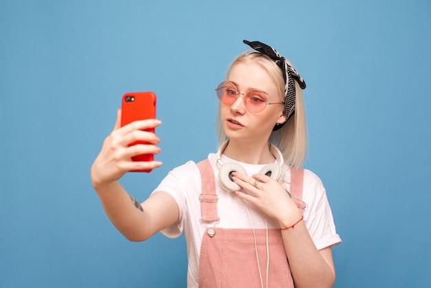 ヘッドフォンと明るい服の女の子が青のスマートフォンでselfieを作る
