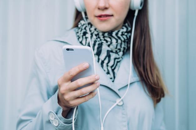 헤드폰과 회색 코트의 소녀는 오디오 북을 수신합니다.