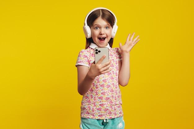Девушка в наушниках держит телефон и показывает ладонь, рада получить уведомление