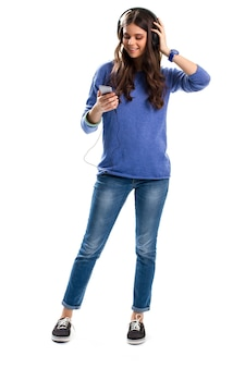 Девушка в наушниках улыбается. женщина с мобильным телефоном. включите свою любимую песню. смартфон с медиаплеером.