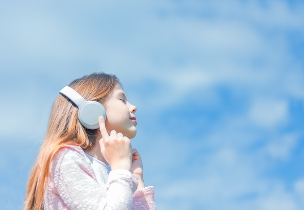 푸른 하늘 배경에 헤드폰 소녀