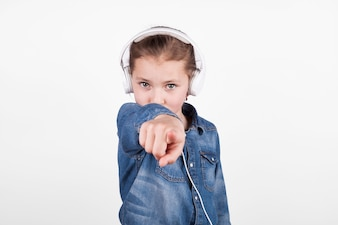 Girl in headphones pointing at camera