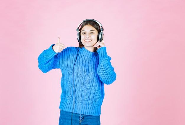 Девушка в наушниках показывает палец вверх на розовом.