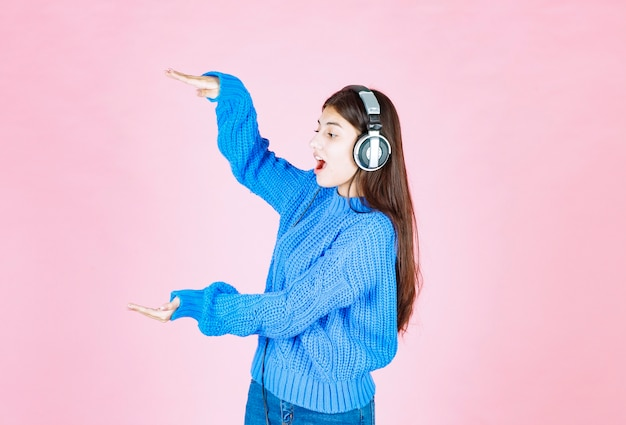ピンクの大きなサイズのサインを示すヘッドフォンの女の子。