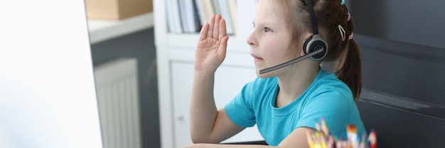 Девушка в наушниках сидит за монитором компьютера и протягивает руки, чтобы ответить на онлайн-уроке