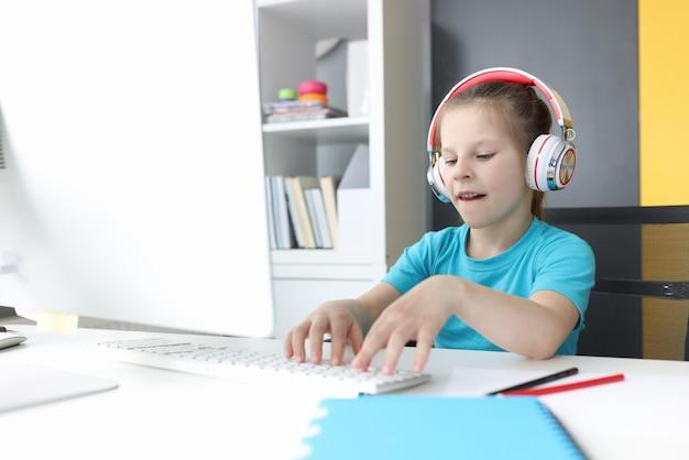 ヘッドフォンの女の子は、コンピューターのモニターに座ってキーボードで入力します