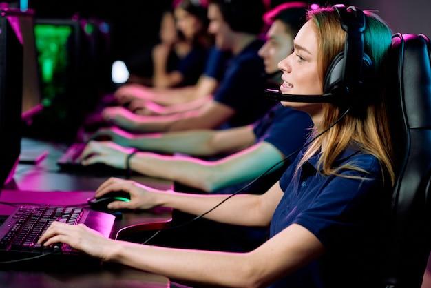 Девушка в наушниках с микрофоном сидит за столом и играет в компьютерную игру в киберспортивном клубе