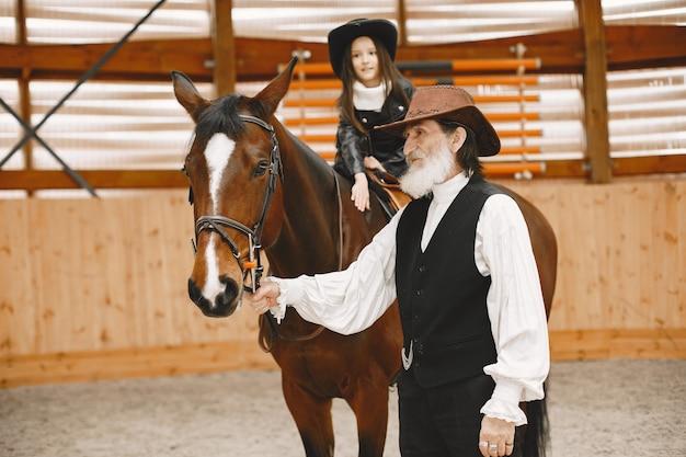 乗馬を学ぶヘルメットの少女。インストラクターは小さな女の子を教えています。