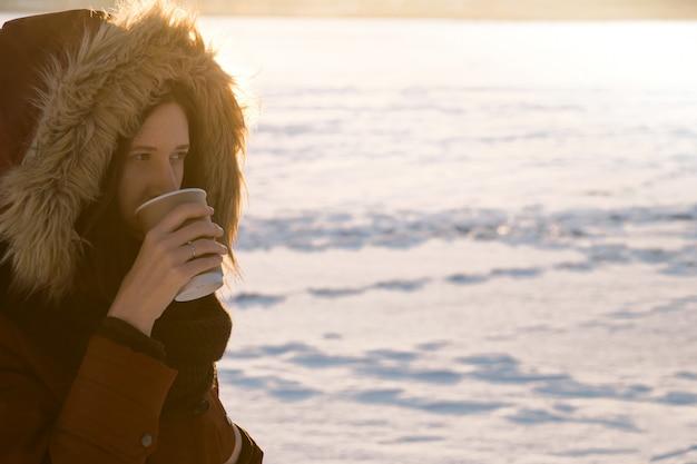 フードの女の子は冬の日にホットコーヒーを飲む