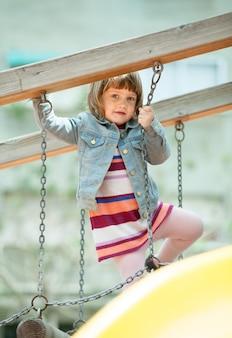 Девушка в куртке на детской площадке