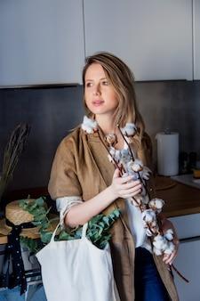 부엌에서 토트 백과 면화 공장 재킷에 여자