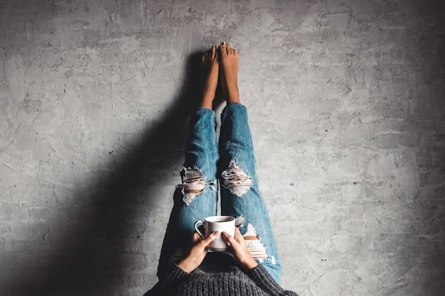 Девушка в джинсах на сером фоне с кофе. читает книгу, прижавшись ногами к стене. обучение, развитие.