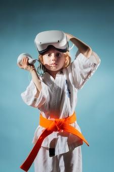 空手の制服を着た女の子がトレーニングを終えた後、仮想現実のヘルメットを脱ぐ