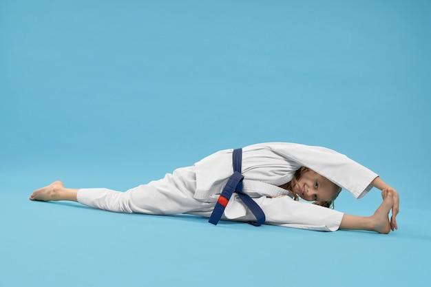 Девушка в кимоно делает шпагат, достигнув ноги.