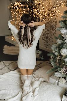 ニットの見通しの女の子は彼女の髪にスカーフを結びます
