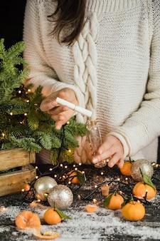 니트 스웨터를 입은 소녀가 크리스마스를 만들어 작은 유리병 만다린과 전나무에 넣습니다...