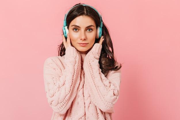 니트 스웨터를 입은 소녀는 더 나은 소리를 위해 헤드폰을 누릅니다. 약간의 미소를 가진 파란 눈의 여자는 분홍색 배경에 카메라에 보인다.