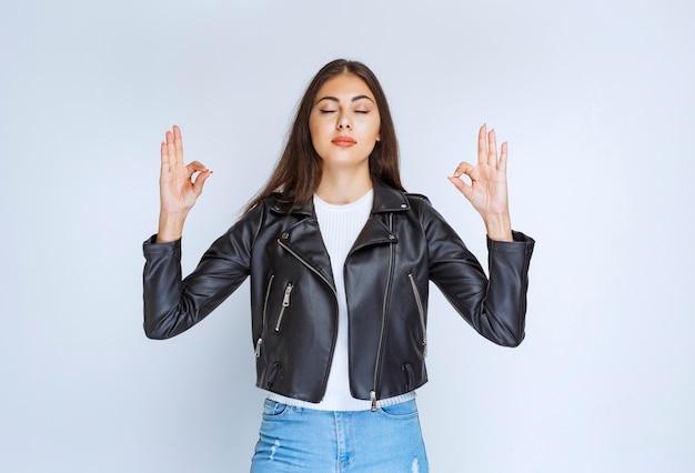 즐거움 기호를 보여주는 가죽 재킷에 소녀입니다.