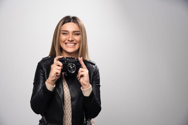 우아하고 긍정적 인 위치에서 그녀의 사진을 찍는 가죽 재킷에 소녀.