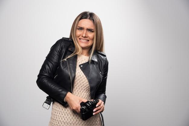 面白いと奇妙な位置で彼女の写真を撮る革のジャケットの女の子。
