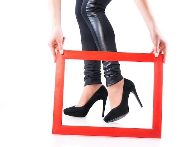革のレギンスと黒のハイヒールの靴の女の子