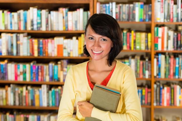 Девушка в библиотеке держит книгу