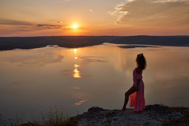 湖の近くの夕日を背景に明るいドレスの女の子