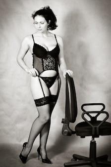 オフィスの椅子の近くに立っているランジェリーの女の子