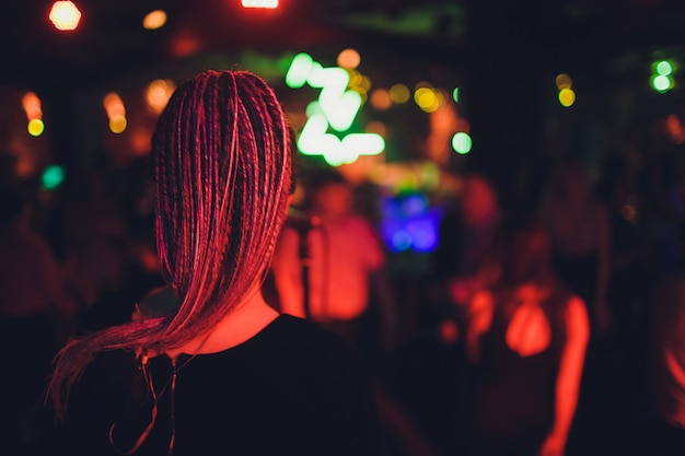무대에서 공연하는 긴 가운에 소녀입니다. 조명 앞 무대에서 노래 소녀. 마이크에서 무대에 서가 수의 실루엣.