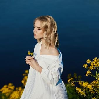 花を手に長い白いドレスを着た女の子が湖の近くに立っています。明るいドレスを着た太陽の下で金髪の女性。完璧なメイクを休む女の子