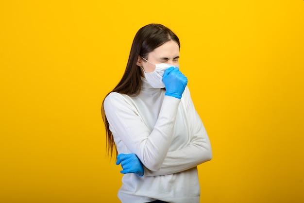 医療用手袋の女の子は、背景に彼女の顔に医療マスクをドレスアップします。呼吸器疾患。 covid-19