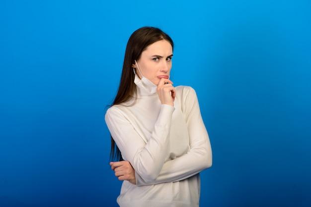 医療用手袋の女の子は彼女の顔に医療用マスクを着せます。呼吸器疾患。 covid-19