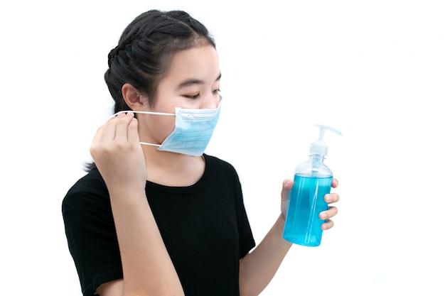 Девушка в медицинской маске очищает руки с антисептическим или спиртовым очищающим гелем с не позволяйте вирусу распространять концепции.